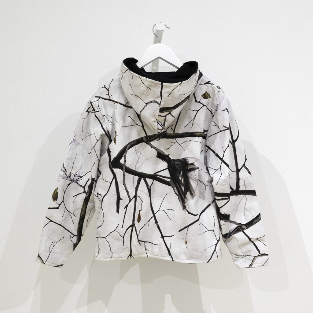 cotton duck cloth vest made of camouflage fabric showing winter branches with plastic bags stuck in them