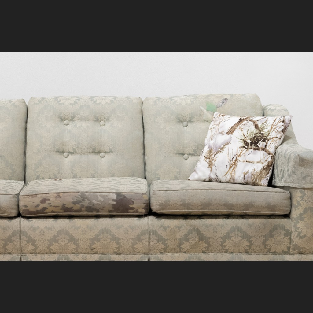 detail of mended couch showing camouflage patch and throw pillow