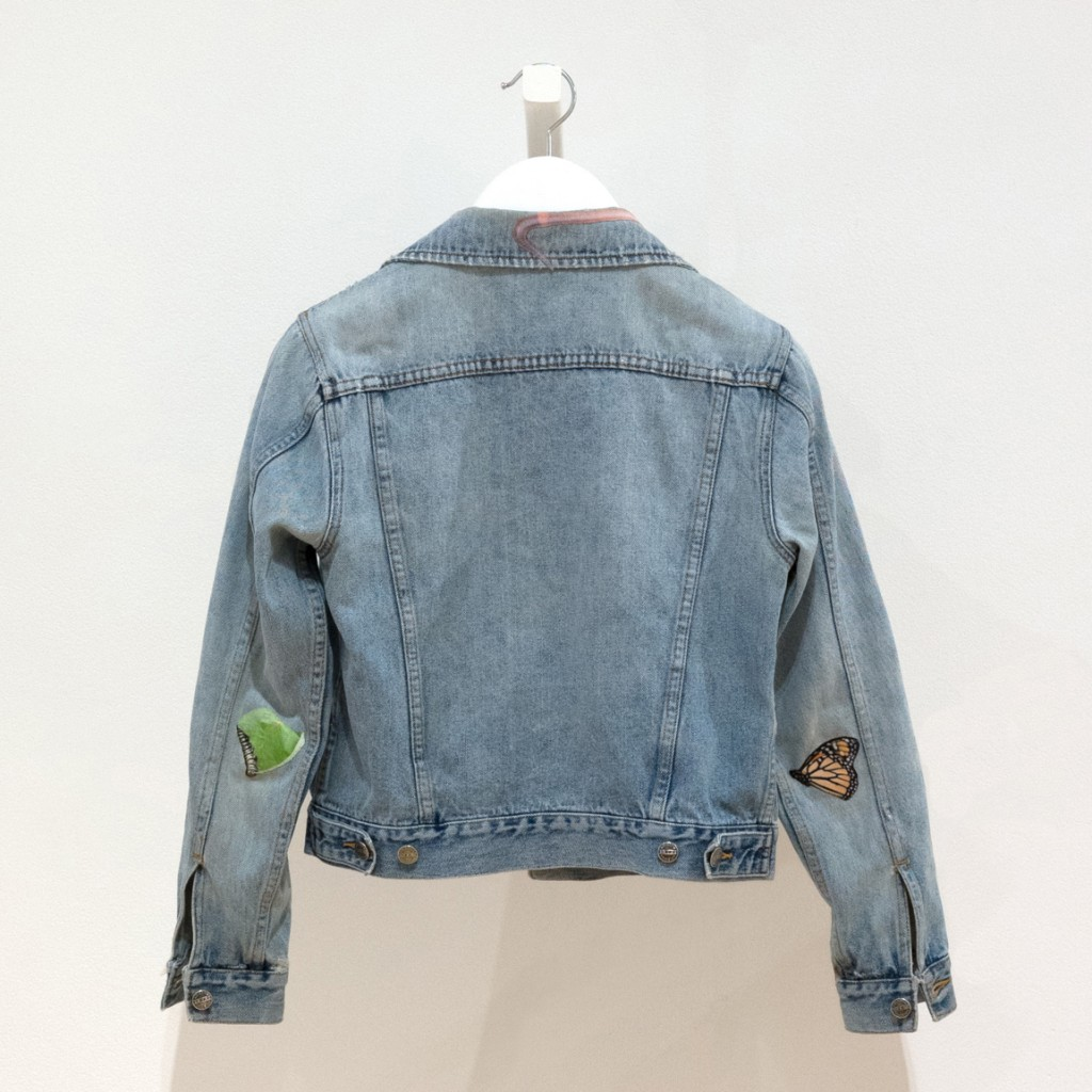 jean jacket with artist-designed patches featuring a butterly, a caterpillar, and a leaf