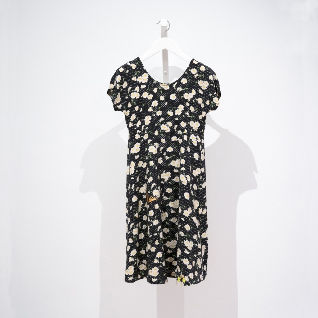 dress with daisies on a field of black with white polka dots, mended with insect patches