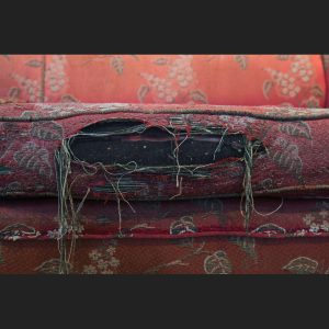 Image of an earth worm poking through a hole in a brocade couch repaired by artist Stephanie Lynn Rogers