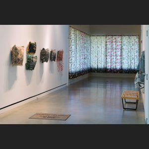 Install view of Make Yourself at Home showing pillows on the wall and curtains
