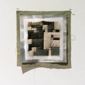 Small sampler piece showing pieced camouflage quilt top with quilt batting, thermal blocking fabric, and cotton backing