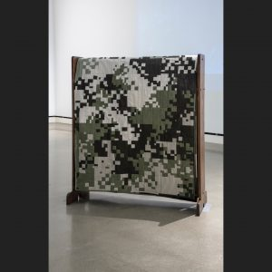 Pieced quilt in digial camo pattern on a quilt rack