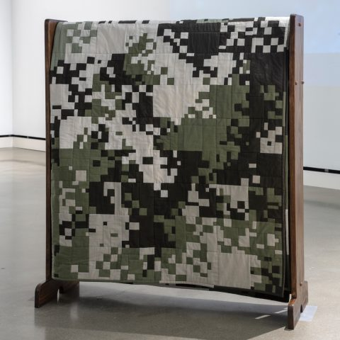 Intricately pieced quilt with digital camouflage pattern on a quilt rack