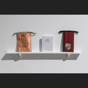 artist designed faraday pouches and zine on a gallery shelf