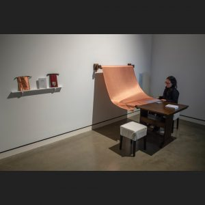 person cutting into a large roll of copper fabric mounted onto the wall