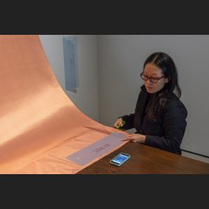 Person cutting copper fabric using a template