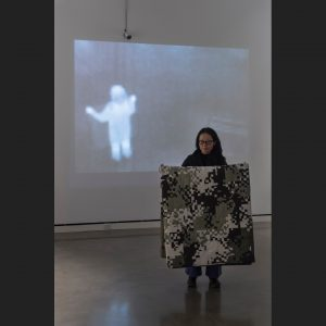 Person holding camouflage quilt with thermal image projected on the wall behind them