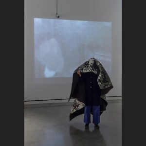 person using a thermal blocking camouflage quilt to hide from a thermal security camera